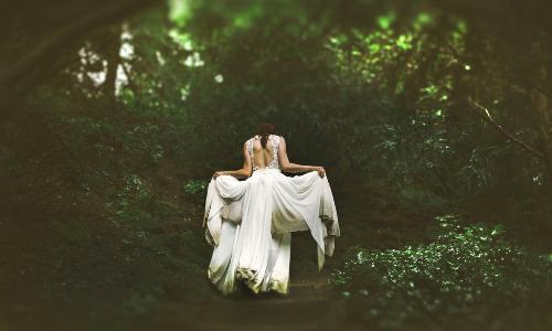 Kvinna med vit klänning går i skogen
